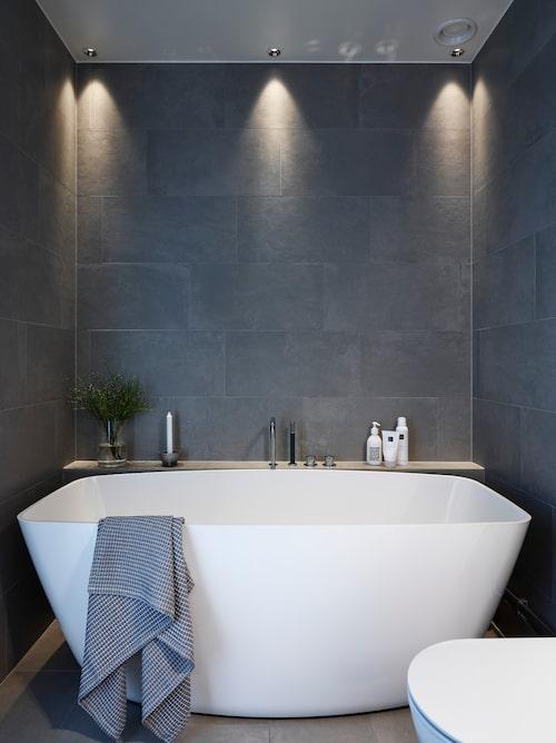 På långväggen vid badkaret har Gun placerat en praktisk hylla av klinker. Badkar, Macro design. Klinker Cement silver, Centro. Takspotlights, Iguzzini.