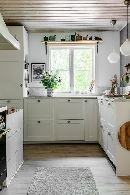 Köket är försiktigt renoverat i husets egen stil. Ovanför fönstret står samlingen av Mattias mortlar och på bänken en av Mirelles fina buketter. Köksinredning, Ikea. Taklampor, Markslöjd.