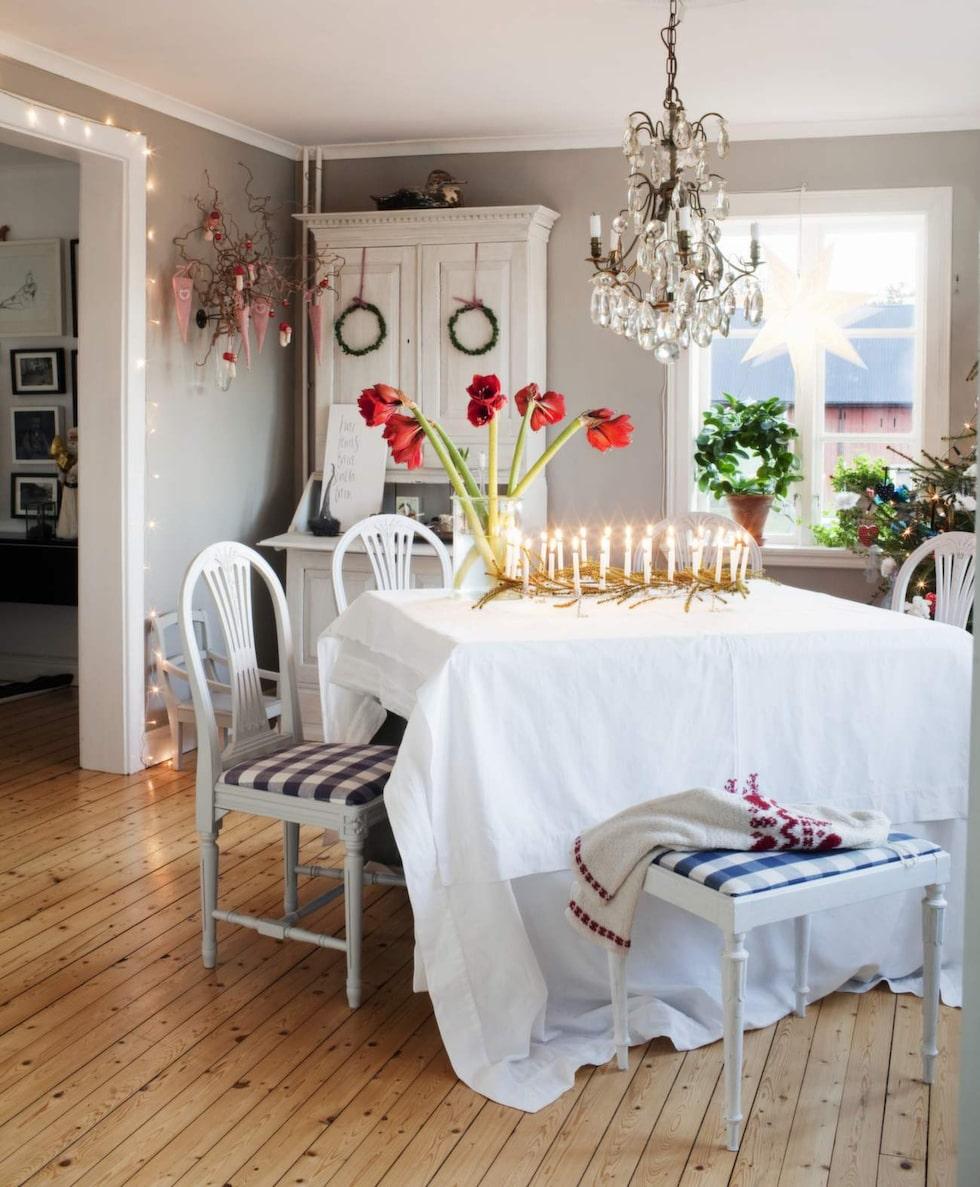 Linda Haglund skapar hellre julstämning med textilier och ljus än med tomtar. Kalenderljusstaken på bordet har 24 ljus och kommer från Utängs antik, liksom takkronan.