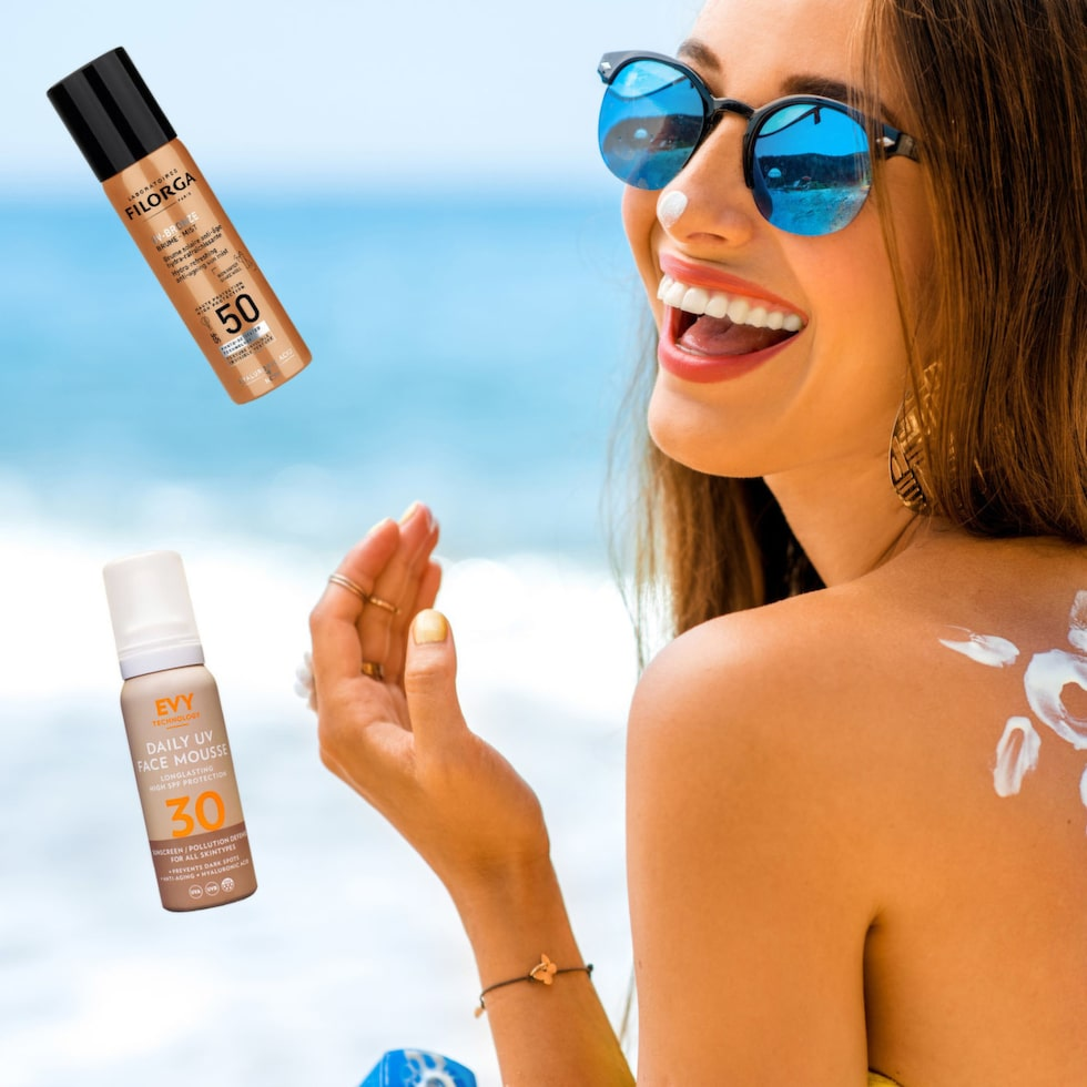 rosshelen young woman with sun shape on the shoulder holding sun cream bottle on the beach