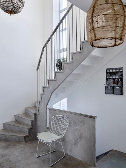 När Patricija och Nenad renoverade bottenplanet så valde de att klä in trapporna med microcement. Italiensk designstol Bertoia Side Chair. Kristallkrona, auktionsfynd.