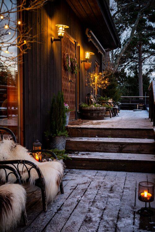 Den välkomnande entrén har försetts med vackra pardörrar som Camilla gärna pryder med julkransar inför julen. Karmstolar, Ikea. Långhåriga fårfällar från Norge.