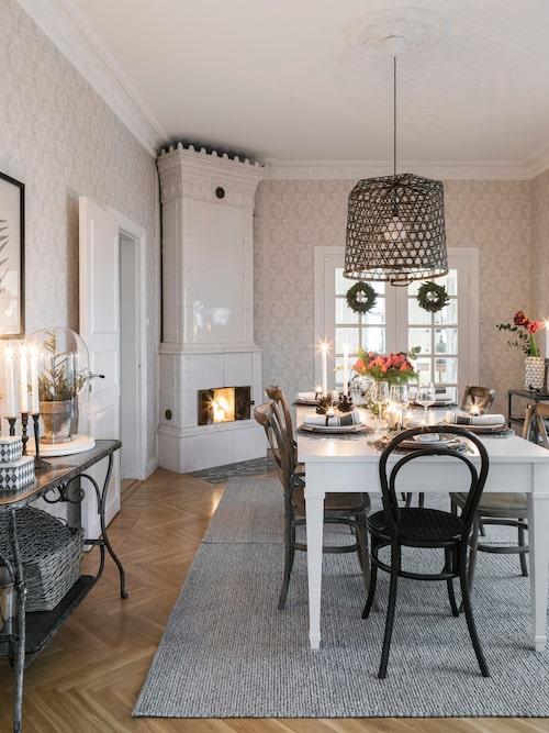 Den vackra matsalen med kakelugn och generös takhöjd är uppdukad till julmiddag. Sofia har gjort lampan ovanför matbordet av en gammal lövkorg. Stolar, Thonet.