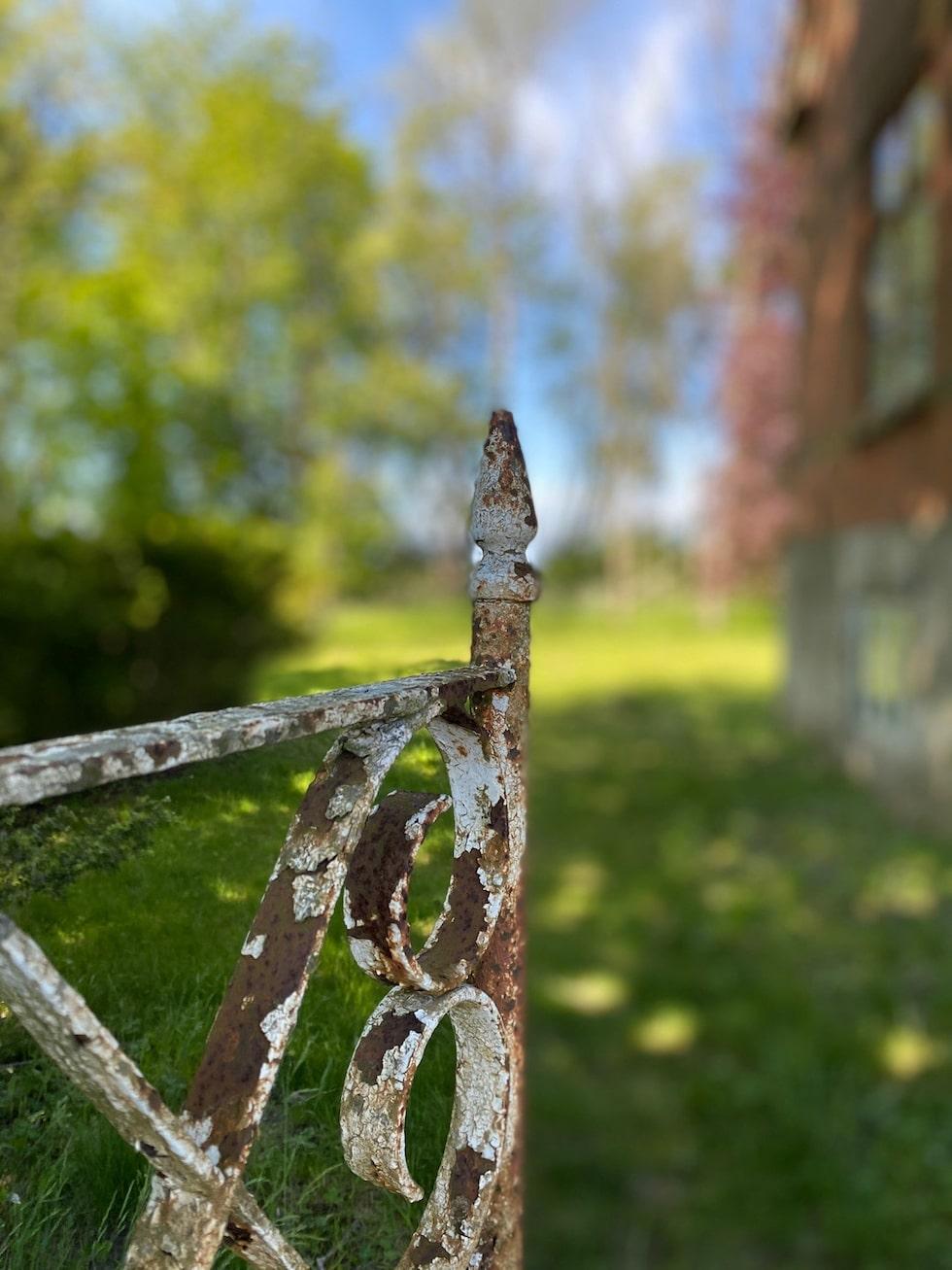 Fin detaljbild på rostig grind som öppnar upp till gården.