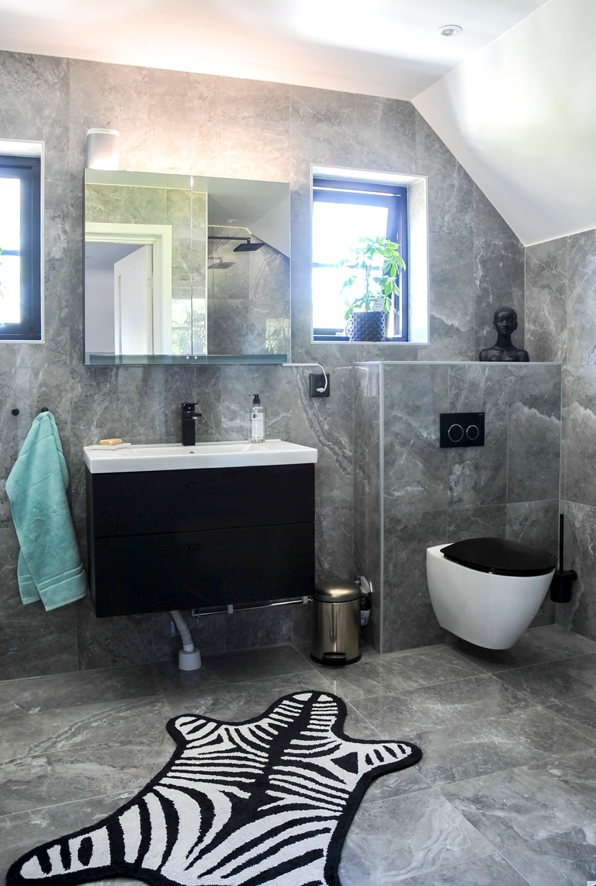 Det helkaklade badrummet har en inredning i svart och vitt. Inredning, INR. Badrumsmatta, Jonathan Adler.