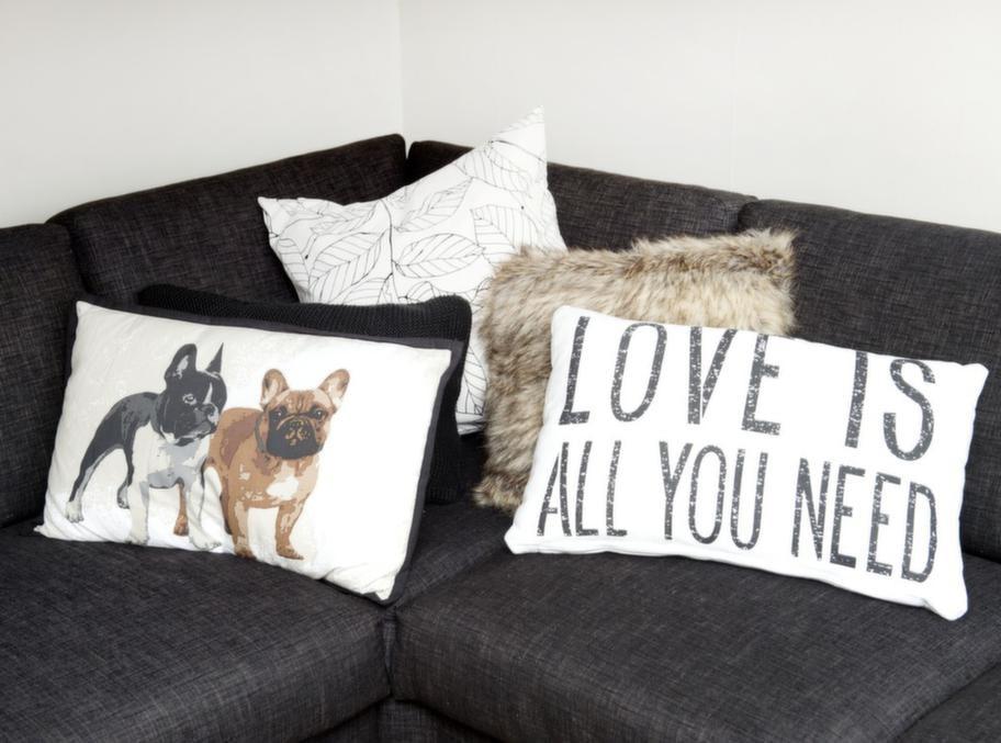 """De många kuddarna har bildat en mysig hörna i den stora mörka soffan som är som gjord för att krypa upp i under kyliga höstkvällar. """"Love is all you need - det stämmer så bra"""", säger Tobias."""