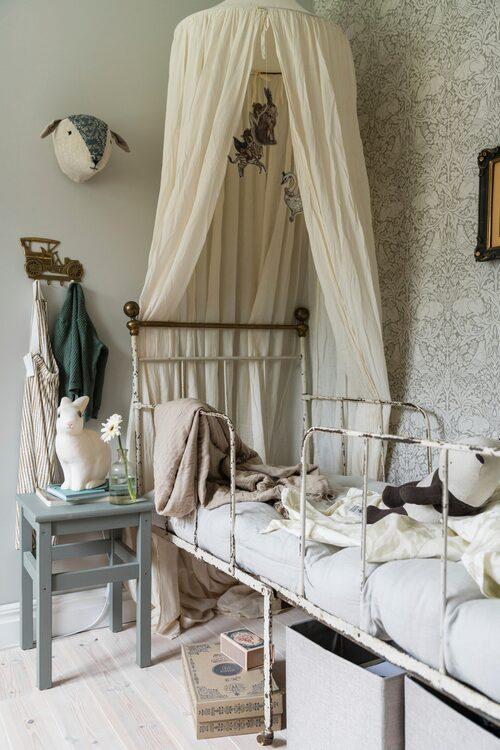 Den gamla sängen är arvegods efter Idas morfar, och nu används den mer som mysplats att krypa upp i. Sänghimlen kommer från Numero 74, kaninlampan från Heico är köpt på Babyshop, fårhuvudet på väggen har Ida sytt själv och bilkroken är köpt på Tradera.