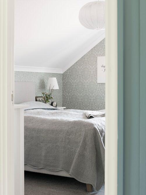 Anna och Marcus sovrum har snedtak. Lampa, från Lamplagret. Överkast och matta, Mio, Tapet, Boråstapeter.