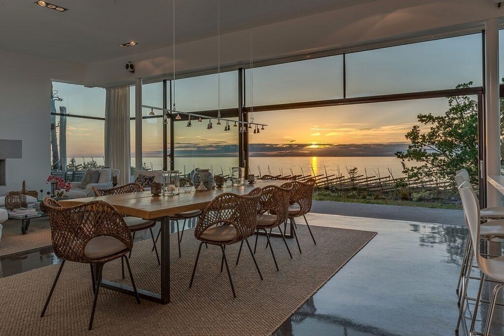 Rakt fram i huset finns ett stort öppet rum med högt till tak och Schuco-dörrar mot havet. Öppen planlösning mot köksdelen.