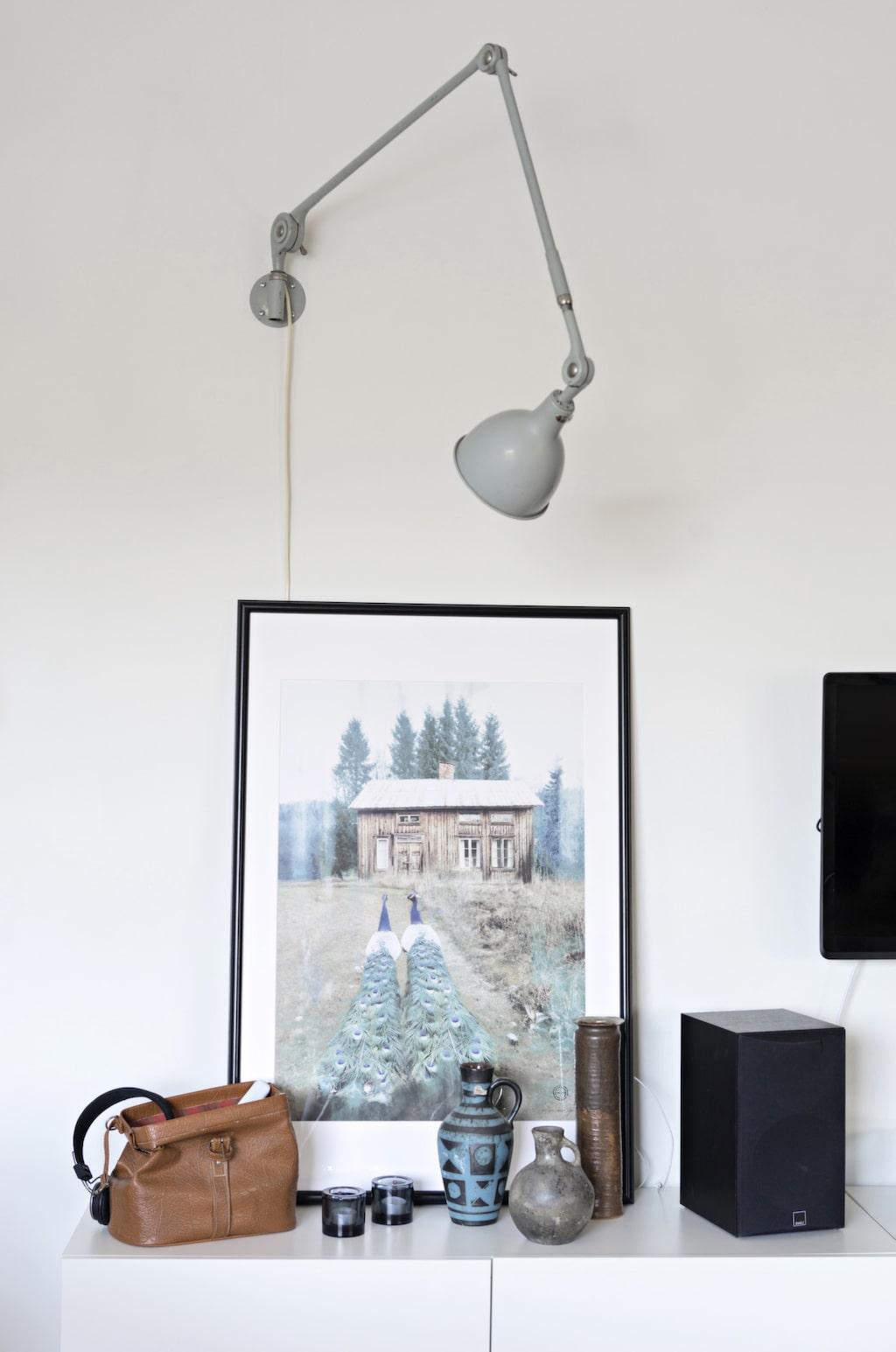 En gammal lampa har fått nytt liv som tavelbelysning. Print Peacock av Camilla Edfors.