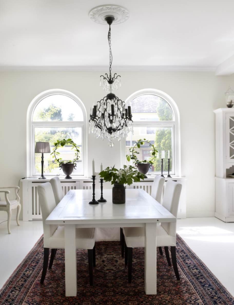 De vackra valvfönstren är som ett smycke för huset. Fönstren är inte  original men huset har i alla fall fått nya fönster efter samma form som  de tidigare spröjsade fönstren. Ljustakarna är från Ilva och urnan från  Härliga hem.