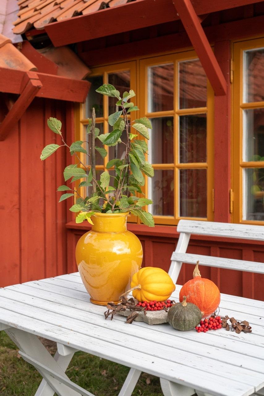 Utomhusmiljöns dekorationer går fint ihop med torpets färgsättningar. Urnan är köpt i Marocko.