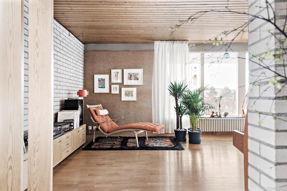 Andra delen av husets stora, ljusa vardagsrum med en musik/vilohörna. Väggar i vit kalksandsten och naturväv samt ekparkettgolv.