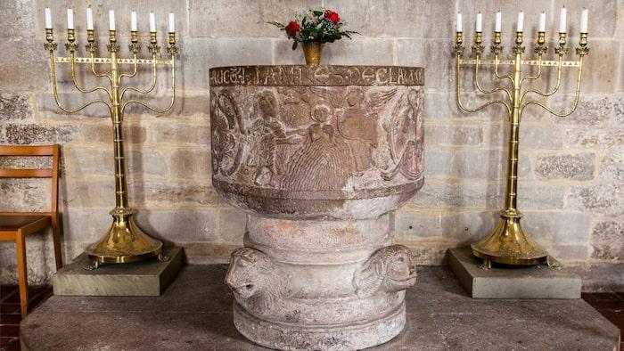 Dalbys 1100-talsdopfunt blev rikskänd redan efter Carl von Linnés besök 1749. Reliefen visar Jesu dop, med en ängel som står redo med en handduk.