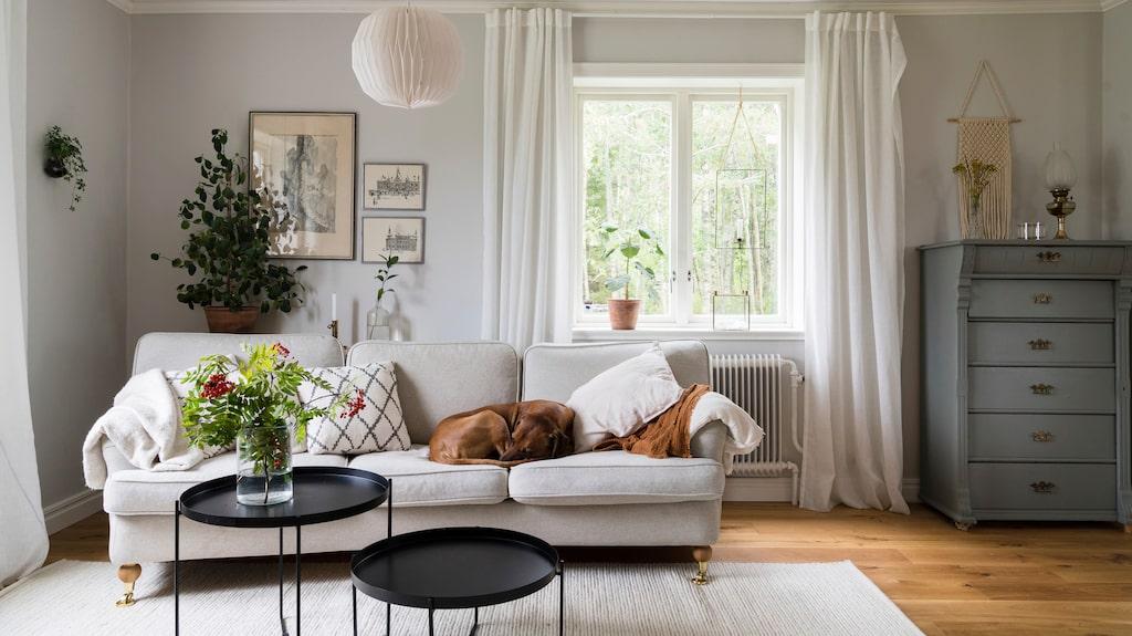 Väggarna i vardagsrummet är målade med matt väggfärg i kulören Lapptussans dusk från Nordsjö, en ljust gråbeige ton som harmonierar fint med både ljusa textilier och svarta inslag. Soffa från Mio, soffbord från Ellos, matta från Mio, taklampa från Clas Ohlson, kuddar från H&M home, Granit och Royal design.