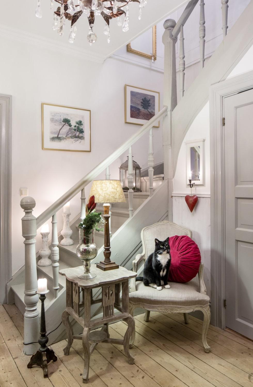 Ljus hall. I den välkomnande sitter familjens katt Kajsamaja och håller koll på vem som går ut och in. Fåtöljen är köpt på en antikmässa och omklädd. Bord från Olsson & Jensen.