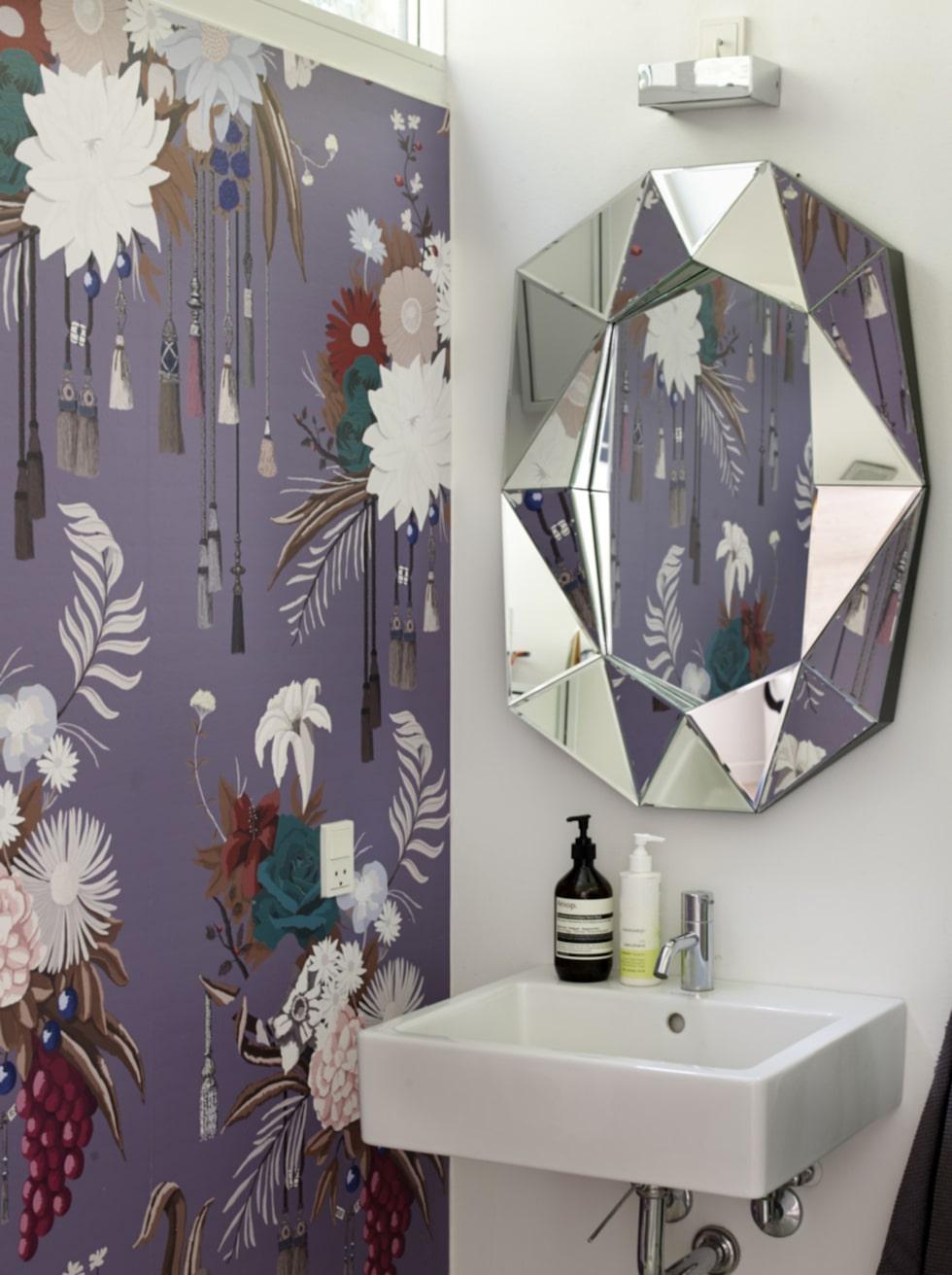 Tapeten i Lauras och Giovannis badrum är designad av Lauras syster Andrea Larsson. Spegel från Reflection by Hugau and Larsson.