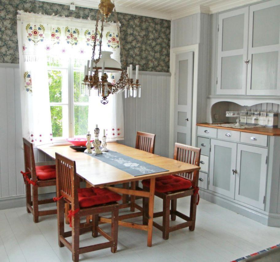 Lantligt kök i grå tonerKristallkronan och möblerna i Bagarstugans kök är arvegods. Tapeten är gammal, tapetrullarna hittade Karin gömda på vinden.