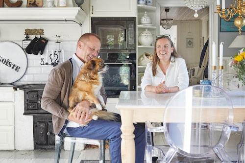 Mira och Christian med hunden Leia i köket som är husets äldsta del. Här samsas den gamla vedspisen med Kartells Louis Ghost-stolar i genomskinlig plast.