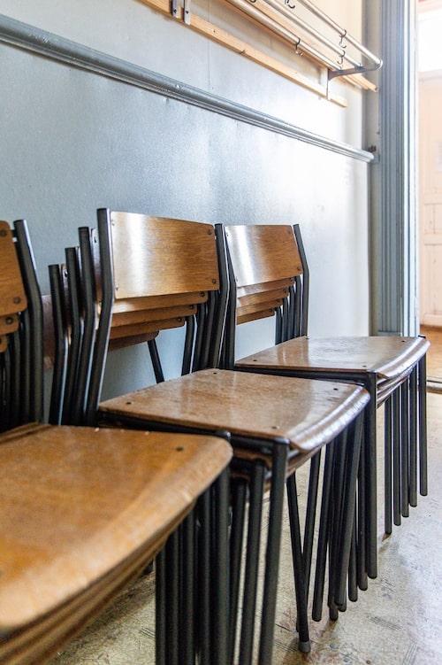 De gamla stolarna uppstaplade i det som en gång var elevernas kapprum.