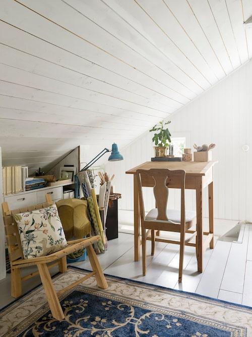 Tidigare bestod övervåning av en kallvind som Linda byggt om till bostadsyta. Här uppe har hon en pysselhörna där pågående projekt huserar. Pulpeten kommer från en gammal skola i Karlstad.
