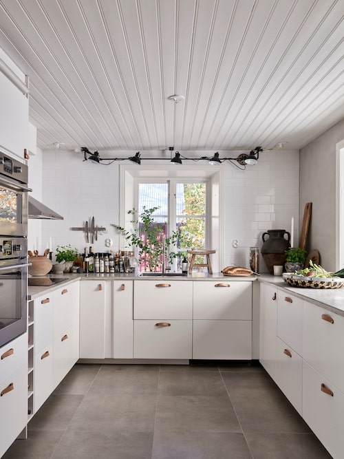 Det nyrenoverade köket går i vitt. Köksstommar, Ikea. Korgar och krukor, Madame Plantier. Ställningen för lamporna har den lokala svetsaren fixat till Anna. Takspotar, Granit.