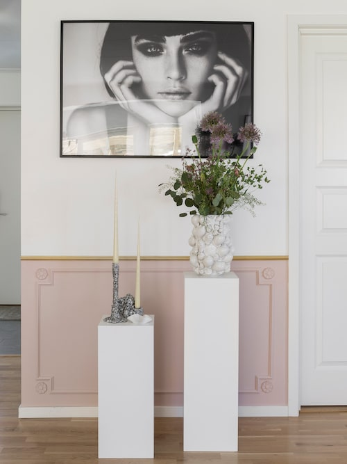 Paret ville inreda med en panel och har satt sin egen personliga touch på den. Panelen målades i rosa och pryddes med lister och snidade blommor. Den översta listen målades i guld. Print, Posterhouse. Vas, By on.