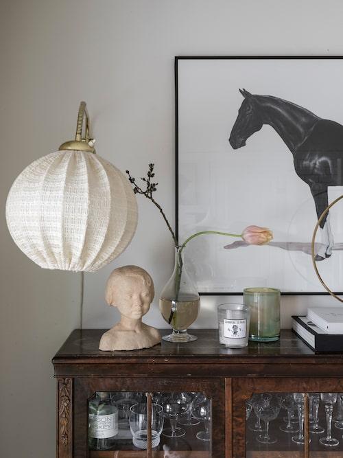 Vitrinskåpet är förstås fyllt med vintageglas. Lampskärm från Retroverket. Doftljus, Oscar&Clothilde. Grön glasljusstake, Artilleriet.
