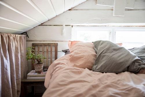 Ett mysigt sovrum med snedtak på loftet. Rosa och grå sängkläder i linne och gardin, från Jotex. Stolen är ett loppisfynd.