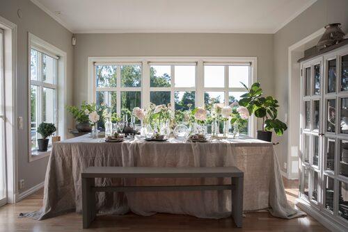 Uppdukat på den ljusa matplatsen. Sittbänken byggde Carin ursprungligen till sin butik. Matbordet har paret själva ritat låtit en lokal snickare bygga. Skåpet är byggt av moduler, Ikea. Duk och linneservetter, Himla och Ohlssons tyger.
