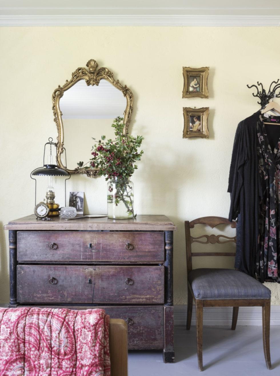 Loppisfynd. I sovrummet fick den gamla byrån och stolarna vara kvar. De lämnades i huset av de förra ägarna. Den vackra spegeln är ett loppisfynd.