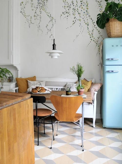 I den gamla kökssoffan har Malin sett sin mormor sitta många gånger. Den har genomgått många färgbyten men är nu vitmålad som köksluckorna. Ovanför soffan har Marika på fri hand målat en murgröna som slingrar sig ner för väggen. Den är inspirerad av Sandberg Wallpapers fondtapet Aralia. Kylskåp, Smeg.