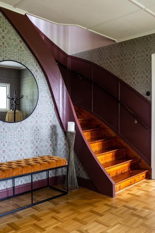 När man kliver över tröskeln till huset möts man av en pampig svängd trappa. Väggarna pryds av tapeten Rosenvinge från Boråstapeter och snickerierna är målade i Jotuns kulör Red Mapl. Bänk, Jotex.
