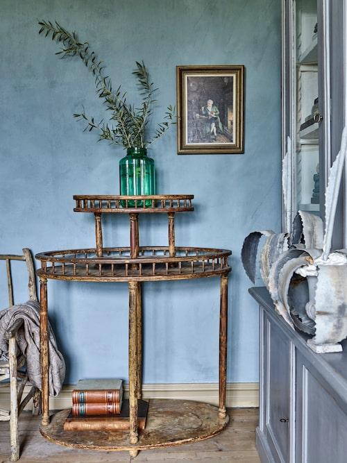 De pariserblå väggarna skapar en fin fond åt det vackra antika blomsterbordet.