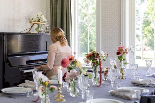 Blommor från den egna trädgården, som rosenskära och dahlia, pryder bordet. Tallrikar Swedish grace, Rörstrand. Assietter, House Doctor. Glas på fot, Cervera. Pianot är ett Blocketfynd.