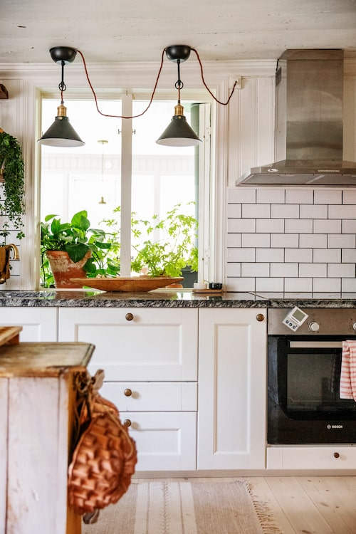 Gammaldags charm i det ljusa och trivsamma köket. Köksinredning, Kitch'n. Lampor, Ljusexperten. Blandare, Sekelskifte. Bänkskiva av sten. Bakformar, Nordic Ware och vintage.