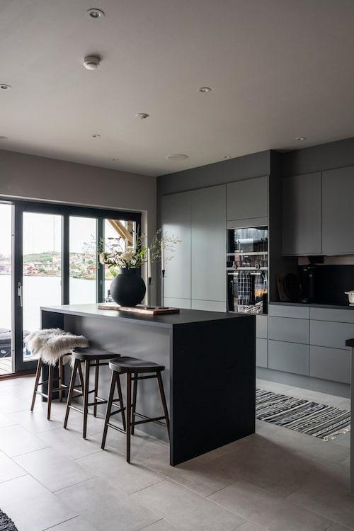 Köket med sin köksö tar vara på utsikten över sundet. Bänkskivan i svart laminat fortsätter upp på väggen som stänkskydd och förstärker kökets karaktär. Mellangrå kök, Arkitekt Plus, Marbodal. Barstolar, Ellos. Lampor över diskbänken, Globen Lighting. Matta, Ikea. Patricia har spraymålat glasvasen i en matt svart färg.