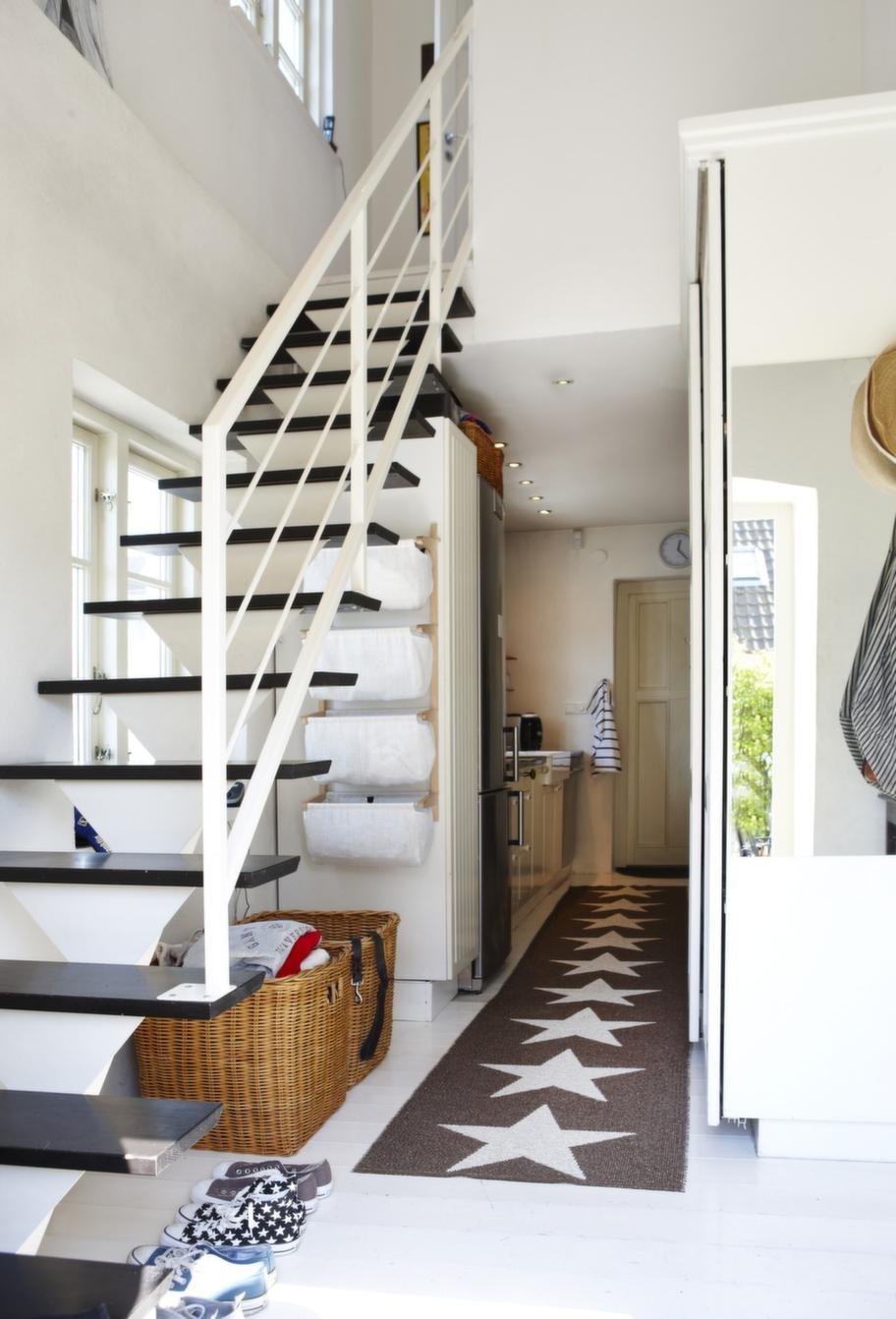 Hallen.<br>Besökaren kliver direkt in i husets hjärta. En luftig trappa leder upp till ovanvåningen, en stjärnbeströdd Pappelinamatta visar vägen till köket.