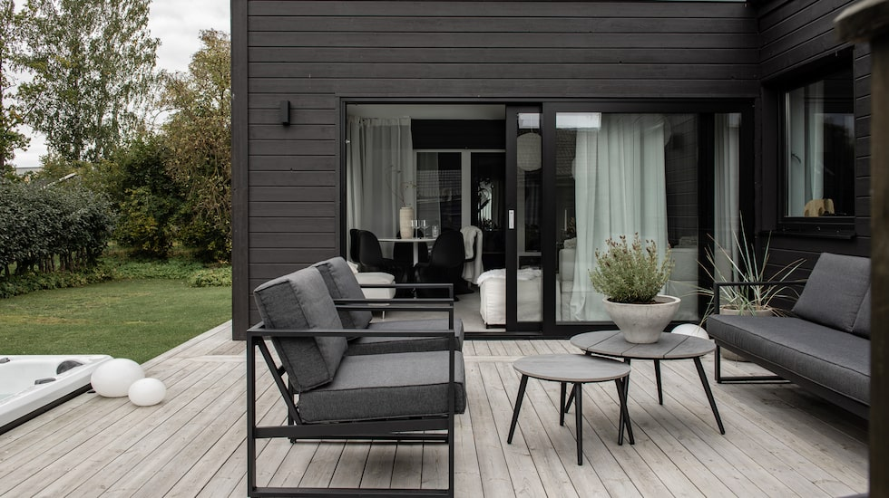 Uteplatsen och uterummet är möblerat i grått, svart och vitt.