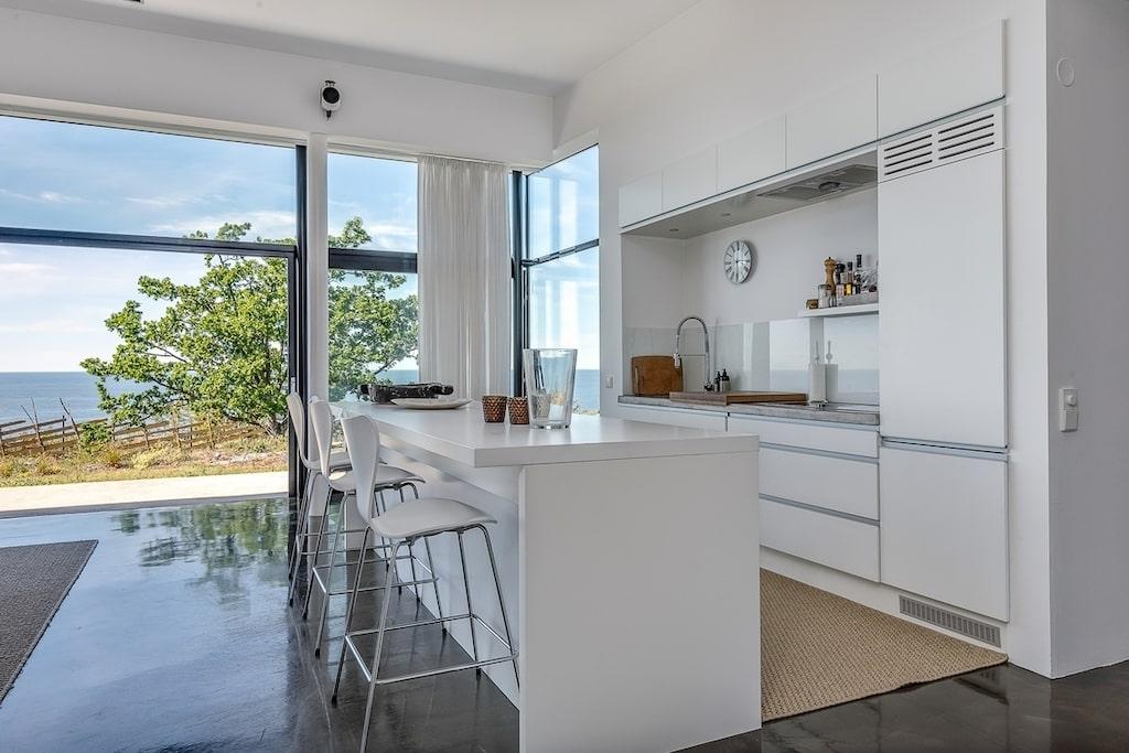 Husets största rum har öppen planlösning mellan vardagsrum, matsal och kök. Vid köksön får man plats många.