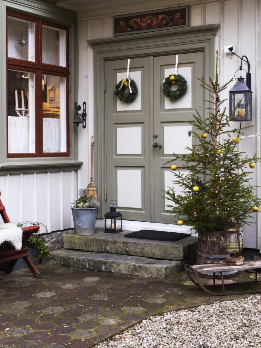 ENTRÉDen gedigna pardörren med allmogemåleri över är som ett smycke för huset. Tarja har pyntat med kransar och gran med äpplen i. Allt för att skapa en ombonad julkänsla redan vid dörren.
