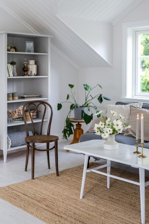 Vardagsrummets soffbord har Elin hittat på föräldrarnas vind. Howardsoffa, Ikea. Stolen är köpt på loppis. Ljusstakarna och takkrona är second hand. Vas och matta, från Ikea.
