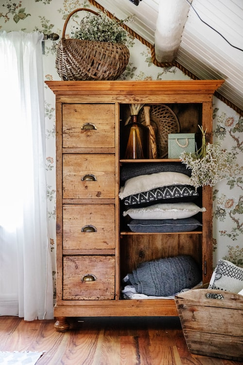 I ett antikt skåp i sovrummet förvarar Linnea kuddar och täcken.