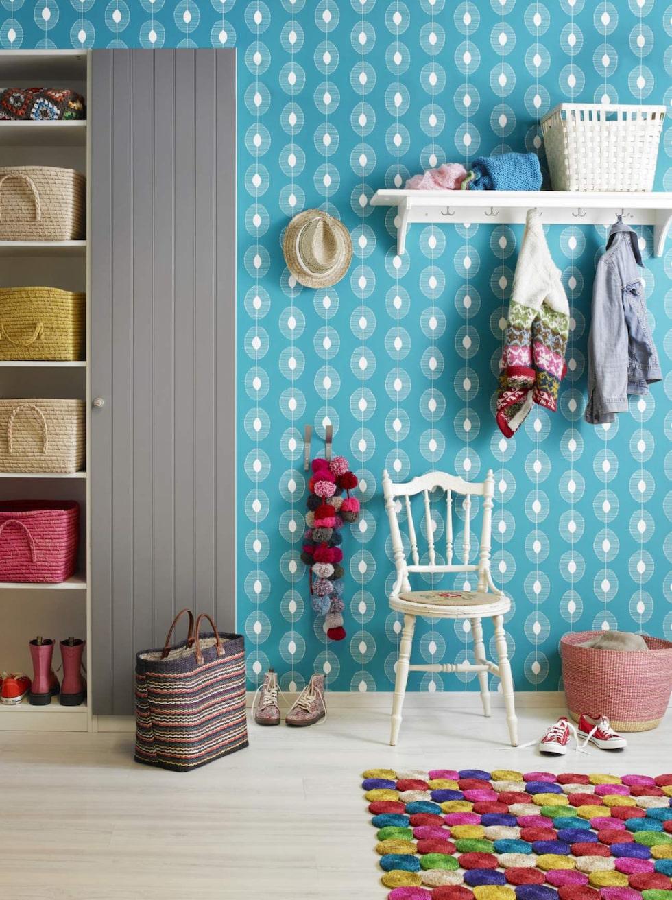 Blå hall. Mysig och välkomnande hall i en lantlig och färgglad stil. Två garderober, den ena med dörr och den andra utan ger all förvaring man behöver. Fina korgar, en loppisstol och den roliga mattan sätter en personlig prägel. Väggen är tapetserad med tapeten Miss Print 2 – MISP1088, Midbec. Pax garderob med dörr, Ikea. Korgar från Rice i skåpet. Matta och rund korg, Afroart. Övrigt privat.