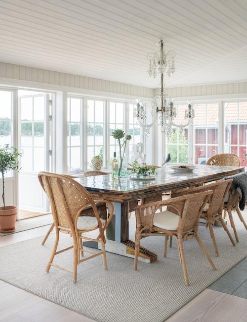 Matplatsen på glasverandan har en fantastisk utsikt över vattnet. Matbordet av spillvirke ger en spännande kontrast mellan gammalt och nytt. Matbord, av Piet Hein Eek. Korgstolar från Ikea och Le Corbusier. Ljuskronan av Muranoglas är antik.