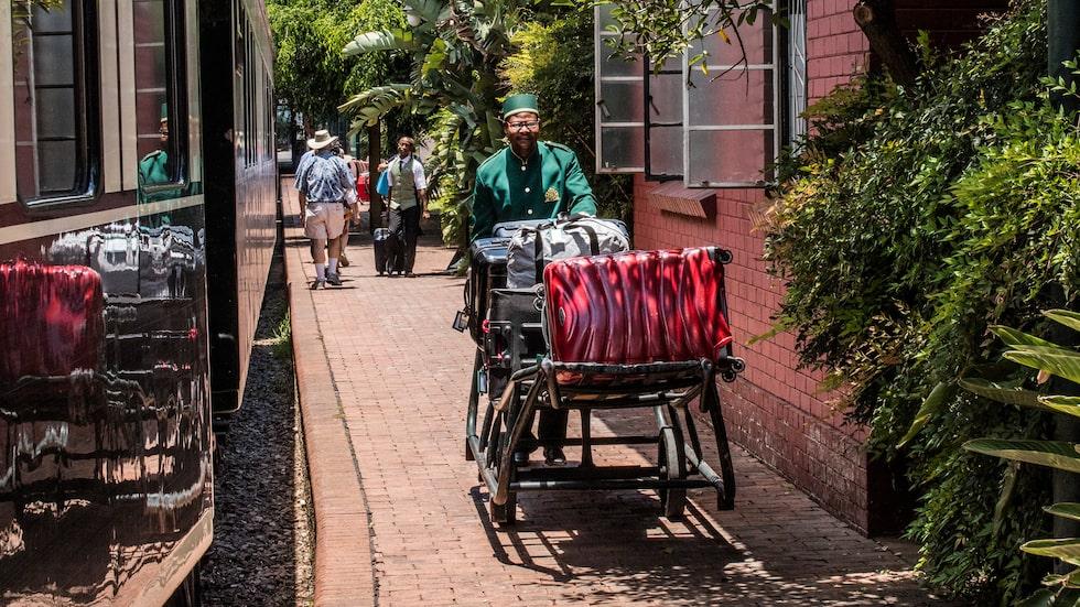 Vid Rovos Rails privata järnvägsstation i Pretoria hjälper piccolor till med väskorna.