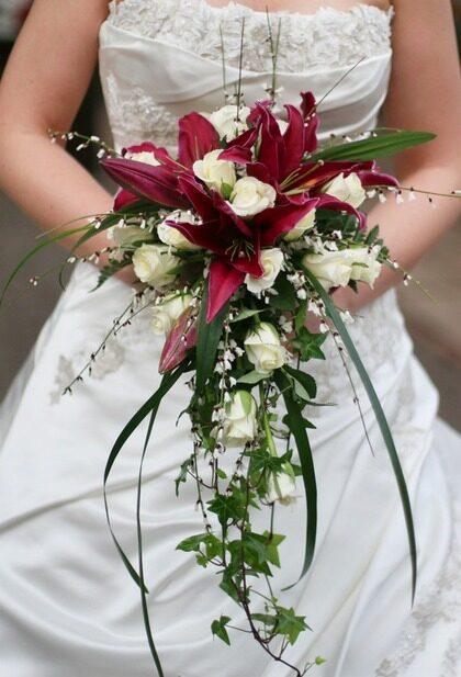LIVFULL. Vinröda liljor och vita rosor med bland annat murgröna i en droppformad livfull bukett.