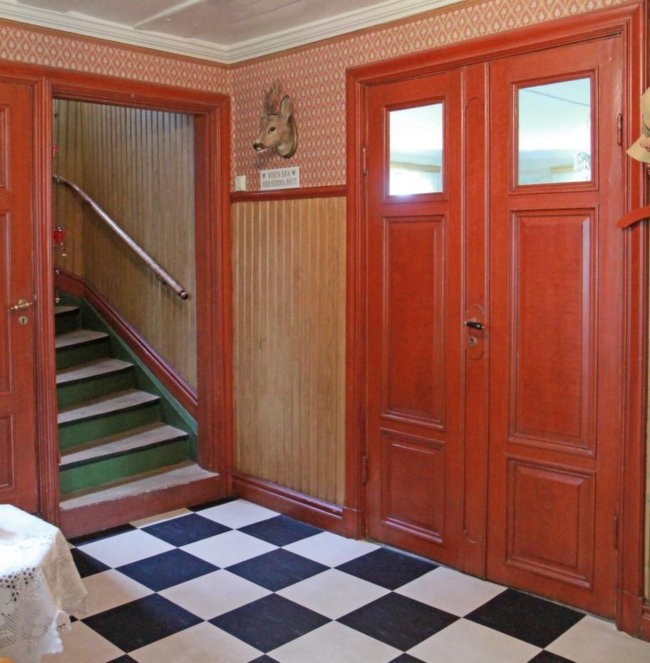Rött & rutigtTrappan till övervåningen i den välkomnande hallen. Alla snickerier är fernissade i gammal stil och golvet är schackrutigt. Den svart- och vitrutiga mattan är nyinlagd.