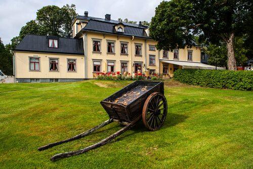 Herrgården Hennickehammar i Värmland kröner den gräsklädda sluttningen mot sjön Hemtjärn.