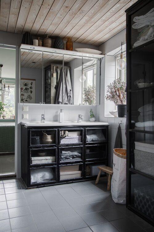 Åsa och Andreas har satt sin egen prägel på badrummet, utan att göra en alltför stor renovering. Tvättstället är inbyggt i en byrå av svart metall.
